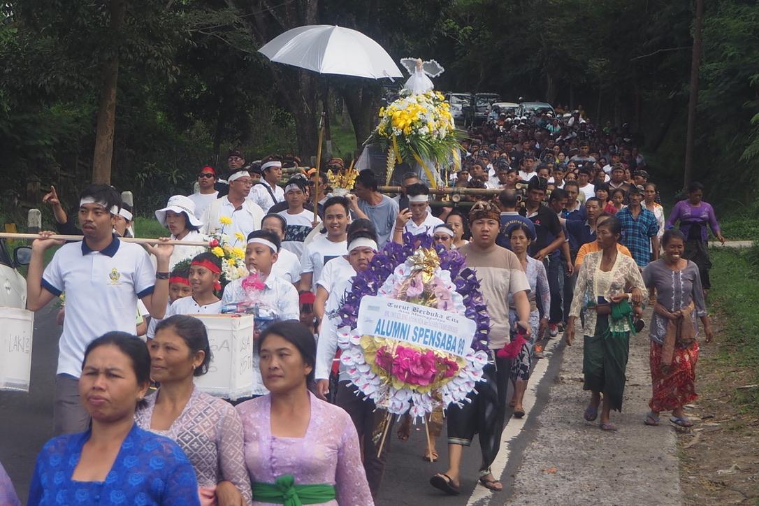 Umat Hindu dan Budha beriringan menuju tempat kremasi. Inilah contoh akulturasi di Baturiti.