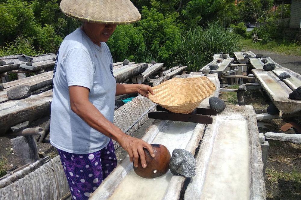 Petani garam Kusamba menggunakan alat-alat tradisional, termasuk pelepah kelapa untuk mendapatkan garam. Foto Juni Antari.