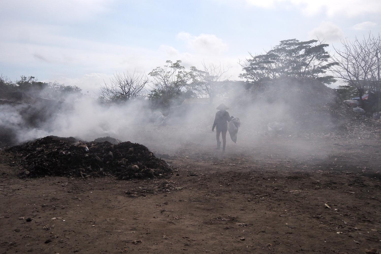 Seorang pekerja berjalan melewati sisa tumpakan sampah yang diolah di TPA Temesi Gianyar. Foto Anton Muhajir